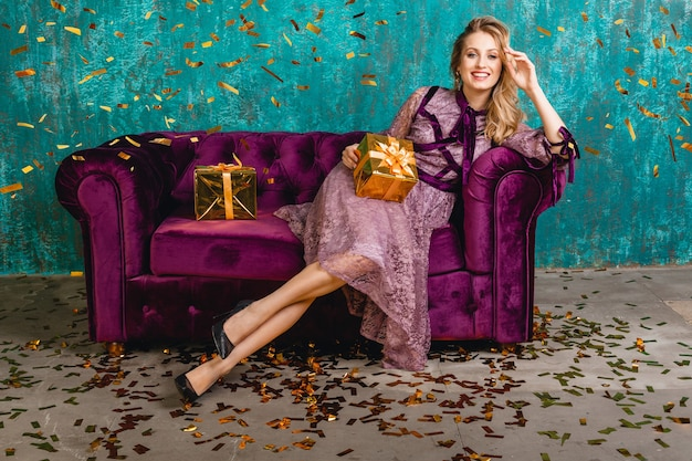 Attractive woman in stylish violet evening luxury dress sitting on velvet sofa with gifts