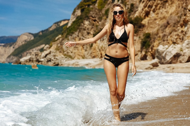 Attractive woman in a swimsuit standing on the beach