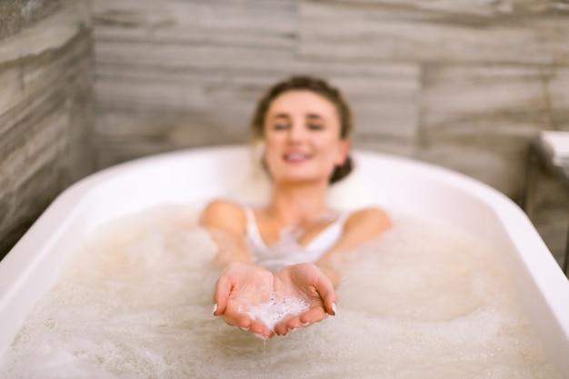 魅力的な女性は、泡でハイドロマッサージ入浴します。カメラ目線の手で泡石けんを示す美しい笑顔の若い女性。