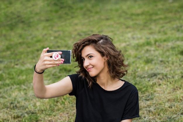 魅力的な女性は、芝生に座ってセルフを取る