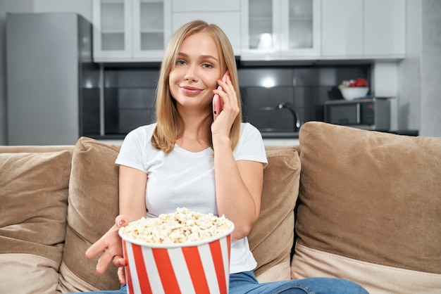 Привлекательная женщина разговаривает по мобильному телефону и ест попкорн