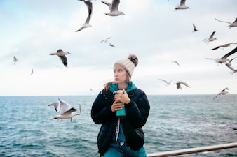 Attractive woman thinking about something, holds thermos near the ocean with seagulls