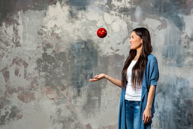 Attractive woman throws up a big red apple standing full length in casual clothes