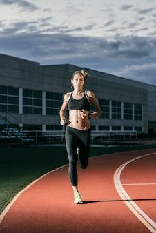 트랙에서 실행 하는 매력적인 여자 트랙 선수. 그녀는 찾고있다