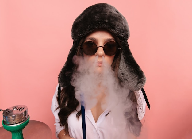 An attractive woman in the traditional russian hat with earflaps and glasses smokes a hookah and enjoys smoking.