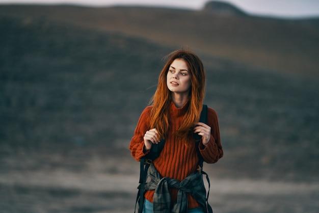 魅力的な女性は山の屋外スカイラインライフスタイルバックパックを旅行します。高品質の写真