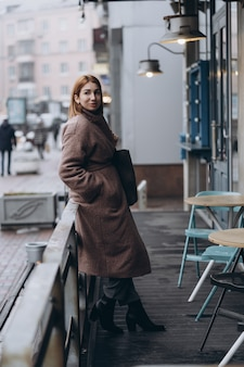 Attractive woman in trench coat on city street