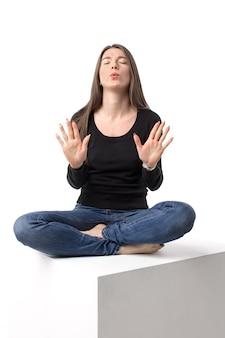 蓮華座でリラックスして深呼吸しようとする魅力的な女性。白い壁に孤立した画像。