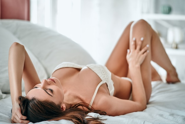 The attractive woman in underwear laying on the bed