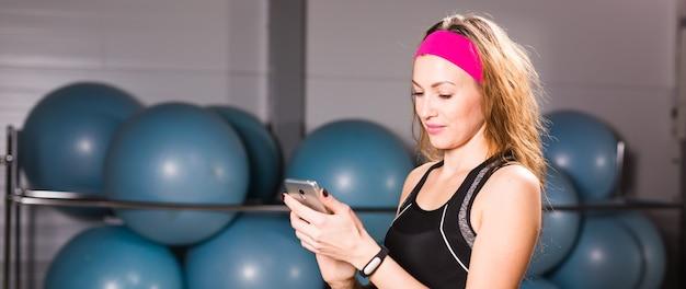체육관에서 휴대 전화 및 피트니스 추적기를 사용하여 매력적인 여자.