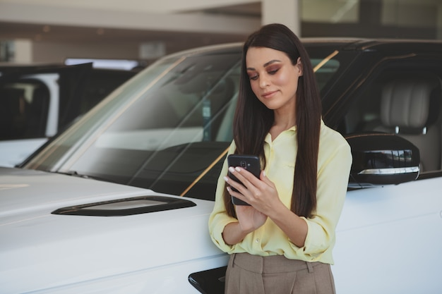 Attractive woman using her smart phone while bying new car