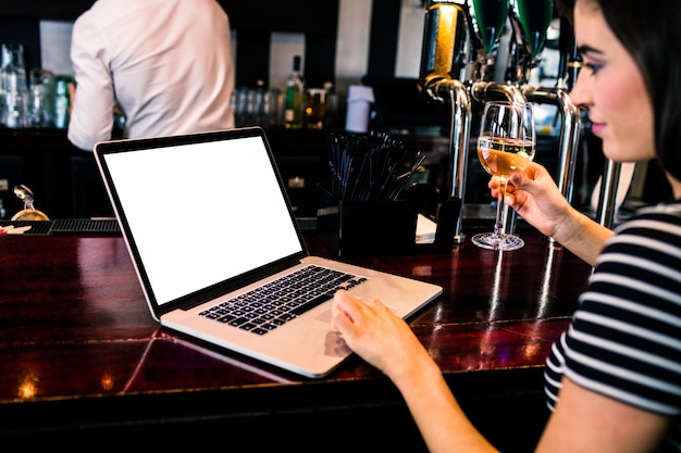 Attractive woman using laptop and having a glass of wine in a bar