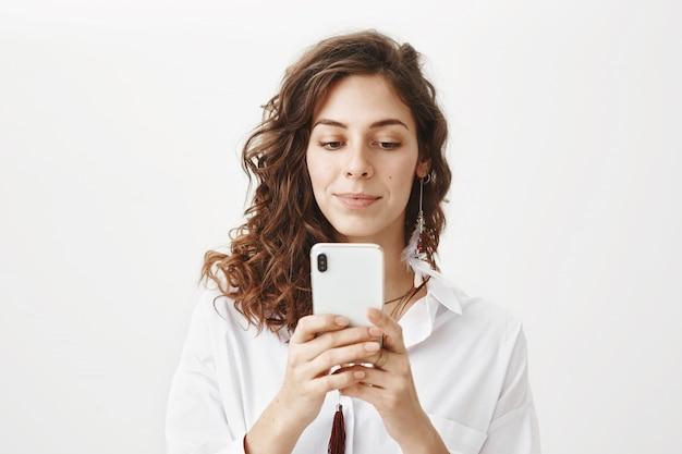 Donna attraente utilizzando il telefono cellulare, scarica l'applicazione
