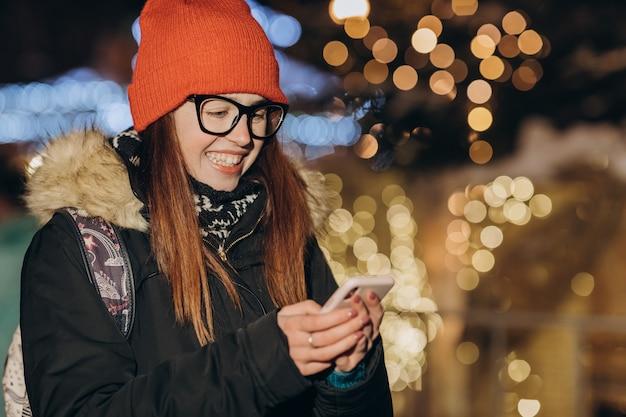 밤 마을의 거리에서 산책하는 동안 휴대 전화를 사용하는 매력적인 여자