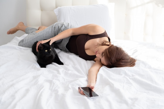 Attractive woman using phone with her black cat, laying together in white bedroom