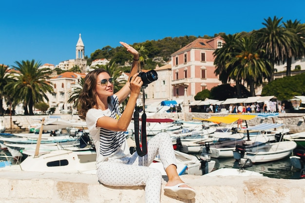 Donna attraente in vacanza in europa in riva al mare in crociera a scattare foto sulla fotocamera