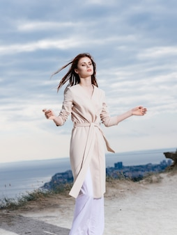 魅力的な女性は、ビーチの砂の熱帯のエレガントなスタイルに沿って歩きます