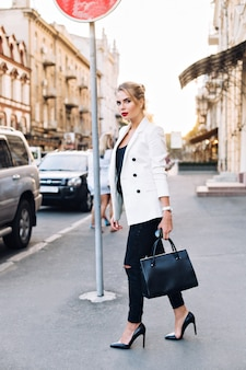 Attractive woman walking on heels in city. she is looking to side.