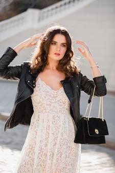 Привлекательная женщина гуляет по улице в модной одежде, держит сумочку, смотрит вниз, в черной кожаной куртке и белом кружевном платье, весенне-осенний стиль