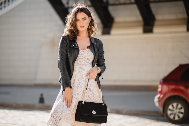Attractive woman walking in street in fashionable outfit, holding purse, looking down, wearing black leather jacket and white lace dress, spring autumn style