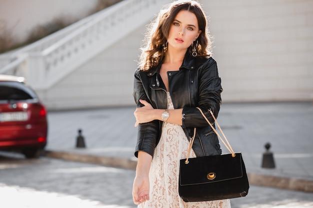 Donna attraente che cammina per strada in abito alla moda, tenendo la borsa, guardando verso il basso, indossa una giacca di pelle nera e abito di pizzo bianco, stile primavera