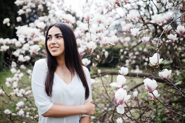 매력적인 여자가 봄 정원을 산책하고 꽃이 만발한 목련 나무의 향기를 즐깁니다.
