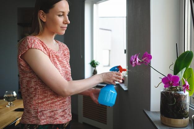 魅力的な女性はアパートで花に水をまく
