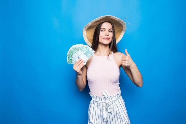 파란색 벽 위에 절연 100 달러, 엄지 손가락 최대의 지폐를 보여주는 밀 짚 모자에 매력적인 여자 착용.