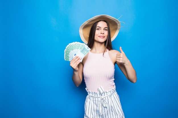 Attractive woman wear in straw hat showing banknotes of 100 usd, thumb-up, isolated over blue wall.
