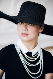 Attractive woman wearing black dress, hat and pearls, sitting on chair