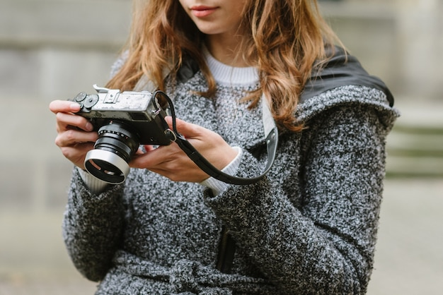 Attractive woman wearing a gray coat holding a vintage camera and looking at it