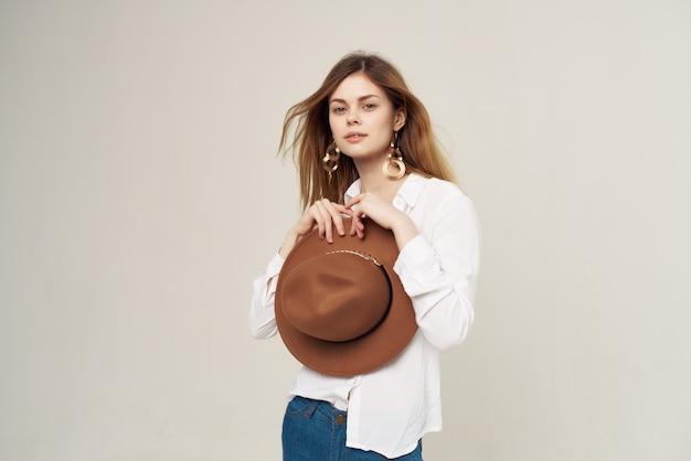 モダンなスタイルの明るい背景のポーズの帽子の装飾を身に着けている魅力的な女性