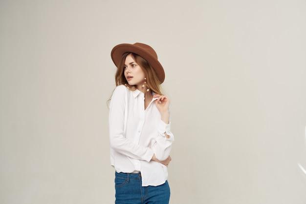 帽子をかぶった魅力的な女性白いシャツライフスタイルファッション高級ポーズ