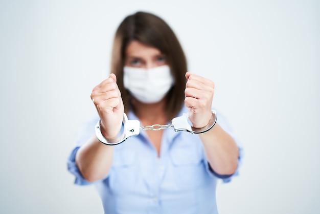 白い背景の上に分離された保護マスクを身に着けている魅力的な女性