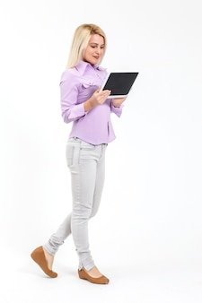 Attractive woman wearing shirt holding tablet standing isolated over white background