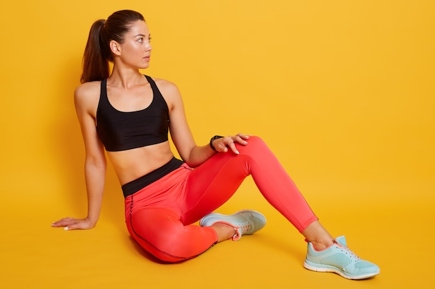 Attractive woman wearing sports bra and leggins, shows slim belly and press, sitting on floor and looking aside