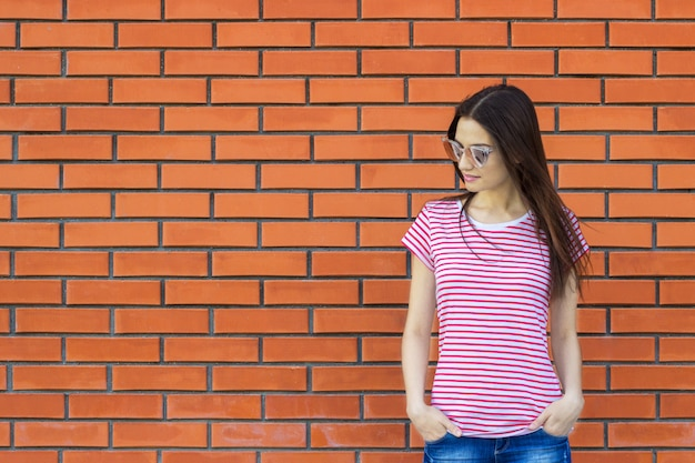 ストライプtシャツとファッショナブルなサングラス赤レンガの壁、盗品ストリートスタイルに対してポーズを着て魅力的な女性。空の