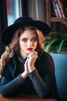 スタイリッシュな黒い帽子をかぶった魅力的な女性。