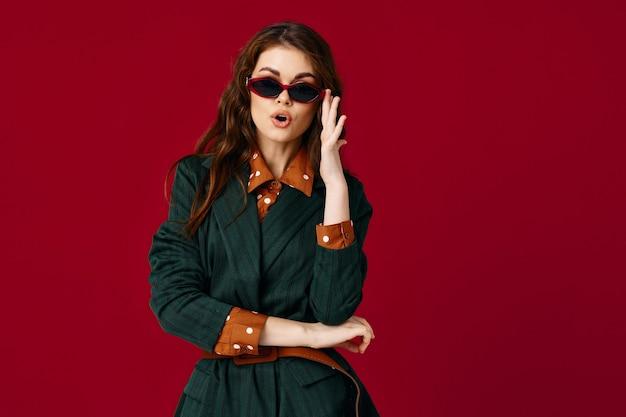 サングラスファッション服グラマー赤い背景を身に着けている魅力的な女性