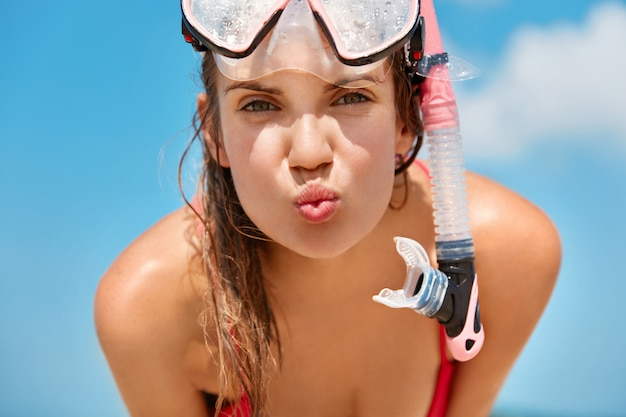 Attractive woman wears snorkel scuba mask, swims in ocean or sea, likes diving, enjoys summer holidays, poses against blue sky
