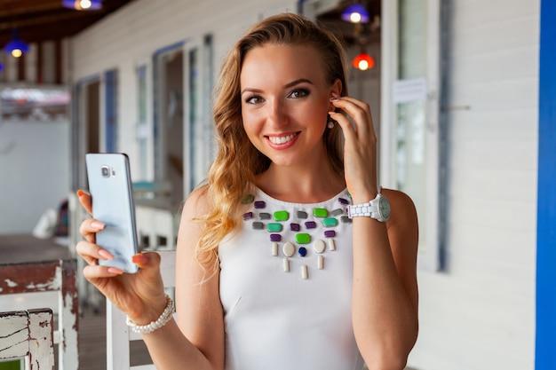 Donna attraente in vestito bianco in caffè estivo in occhiali da sole utilizzando il telefono che cattura foto