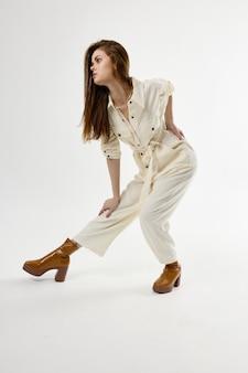 魅力的な女性の白いジャンプスーツのファッションブーツが前に曲がっている