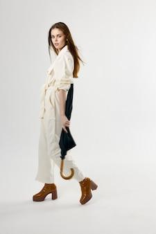 Attractive woman in white jumpsuit umbrella fashion clothes studio