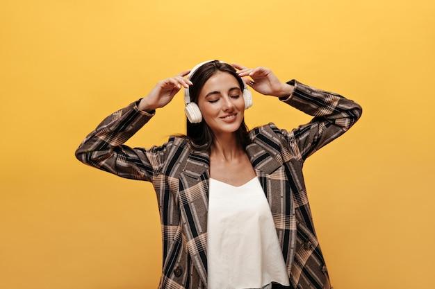 Donna attraente in maglietta bianca, giacca oversize sorride ampiamente e indossa le cuffie