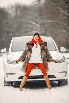 Attractive woman in wintertime outdoor with white car