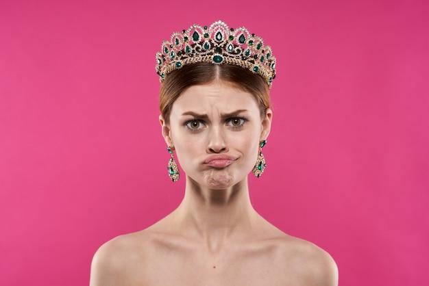 彼女の頭の上の王冠を持つ魅力的な女性化粧装飾ピンクの背景