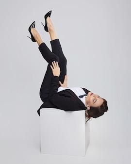복고풍 헤어 스타일으로 매력적인 여자는 남자의 정장에 포즈. 흰색 배경에 스튜디오에서 사진 촬영