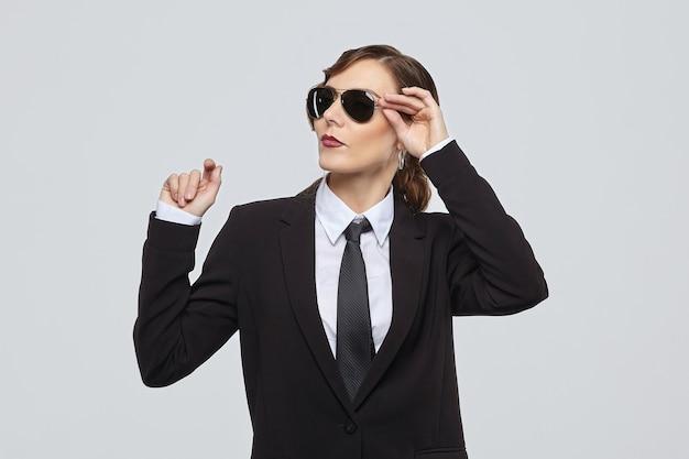 Привлекательная женщина с ретро-прической позирует в мужском костюме и солнцезащитных очках
