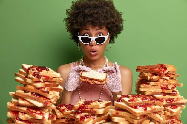Attraente donna con i capelli afro circondato da panini gelati al burro di arachidi