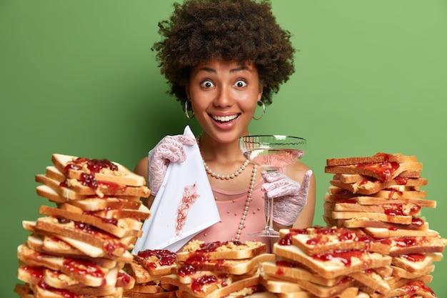 ピーナッツバターのゼリーサンドイッチに囲まれたアフロヘアーの魅力的な女性 無料写真